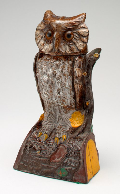 owl perched on log; brown and black glass eyes; owl turns its head to PL