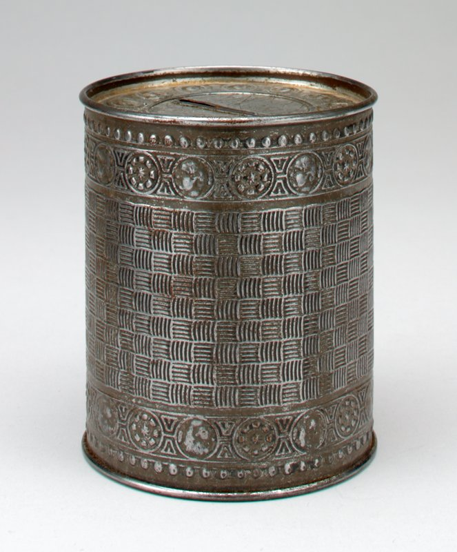 silver patina; can-shaped; stamped circles on top; basketweave design on body, with top and bottom bands of heads in profile and geometric designs