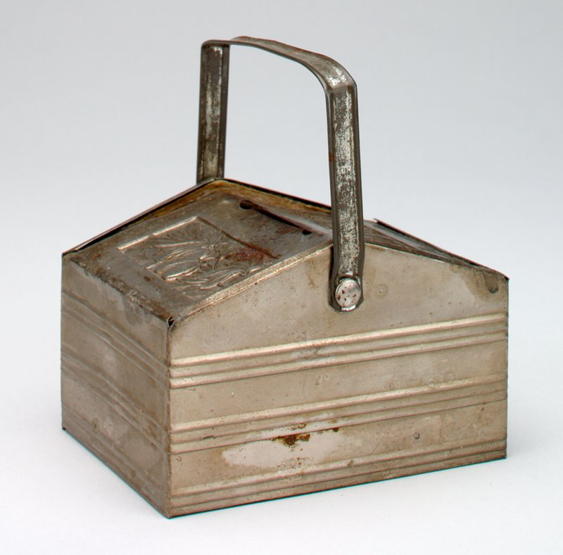 picnic basket shape with sloping cover; handle; stamped design of fruits on vine; silver patina