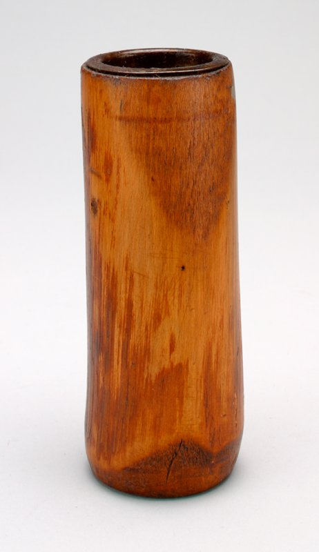 bank in the form of a wooden cylinder with a metal top for coin slot; top and bottom are flat; woodgrain shows plainly; slight taper inward on bottom edge; circle within a circle carved on bottom
