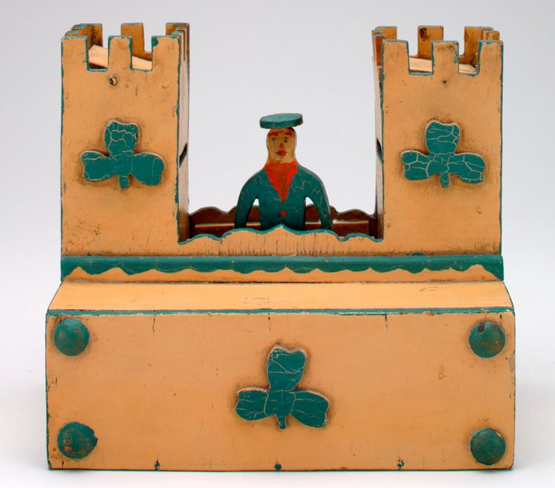 rectangular tan building with twin crenulated towers; painted green decoration in the form of edging, shamrocks and raised dots; wooden man between towers with painted face, wearing red and blue with a round hat; man moves on a metal rod