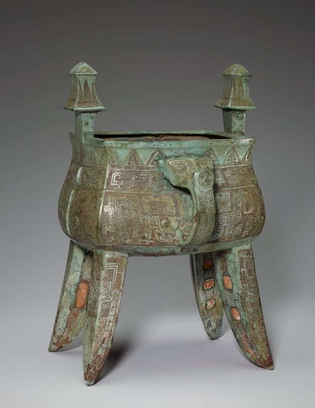 Kia with four spread legs, inscribed. The decor of the body, S-shaped in profile, displays the usual elements of a bodied t'ao-t'ieh flanked by vertical dragons and, in the neck belt, beaked dragons with a band of rising blades filled with disolved cicada figures. The flanges on the body are low, narrow and unscored. Scores appear, instead, on the horns of the large t'ao-t'ieh and on parts of the antithetical beaked dragons appearing in a complicated arrangement on the outer surfaces of the legs. On the top of the handle is a t'ao-t'ieh with C-shaped horns, its mouth gaping over a finely-drawn cicada. The uprights, square at the base, with an incurving profile, are decorated with a spiral band, slender rising blades, and t'ao-t'ieh masks on the tops. Patina grey-green