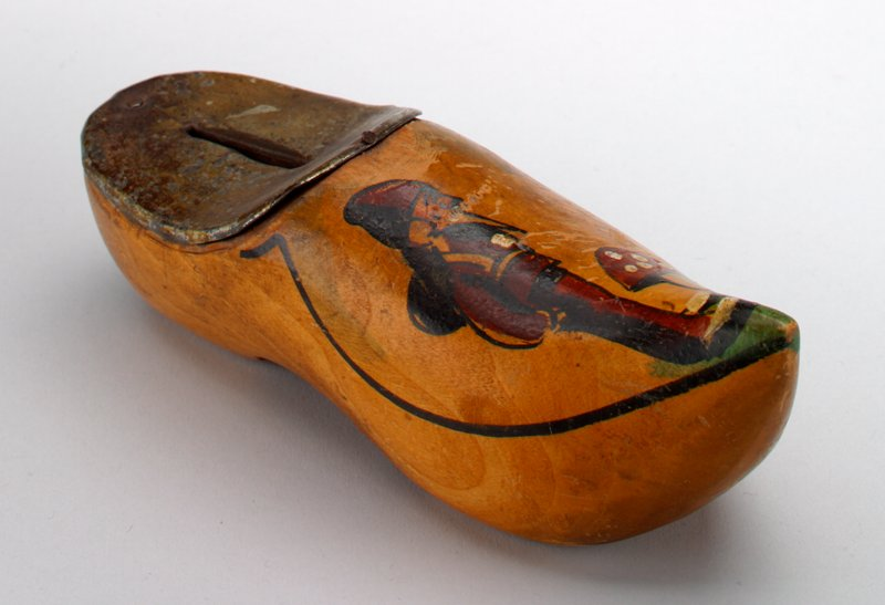 "wooden shoe with pointed toe; painted elf dressed in red beside a spotted mushroom; metal cover with slot for coins; ""Utrecht"" painted in black on side"