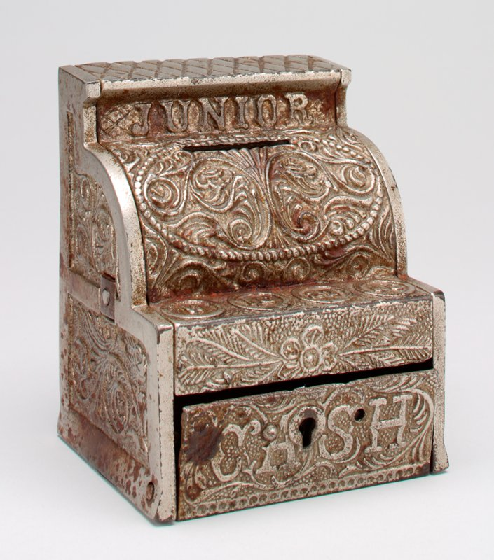 """Junior"" at top front; ""Cash"" on front of drawer; scrolls and floral motifs cast in relief on all surfaces"