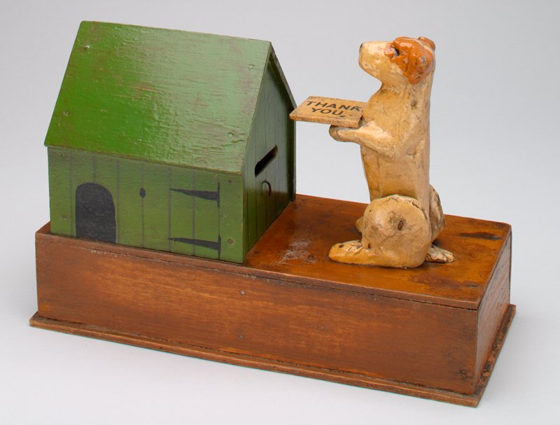 brick shape base; green dog house with black details and coin slot; dog, tan and rust, holding tray, facing house; dog bows when coin is placed on tray