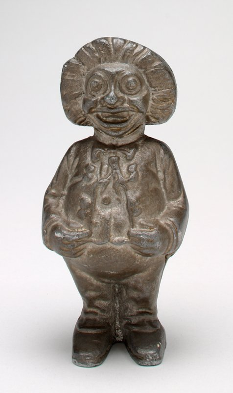 """silver figure of man with large smile; """"pop"""" eyes; bushy hair; wearing tail coat, vest, bow tie; black color; coin slot in back"""