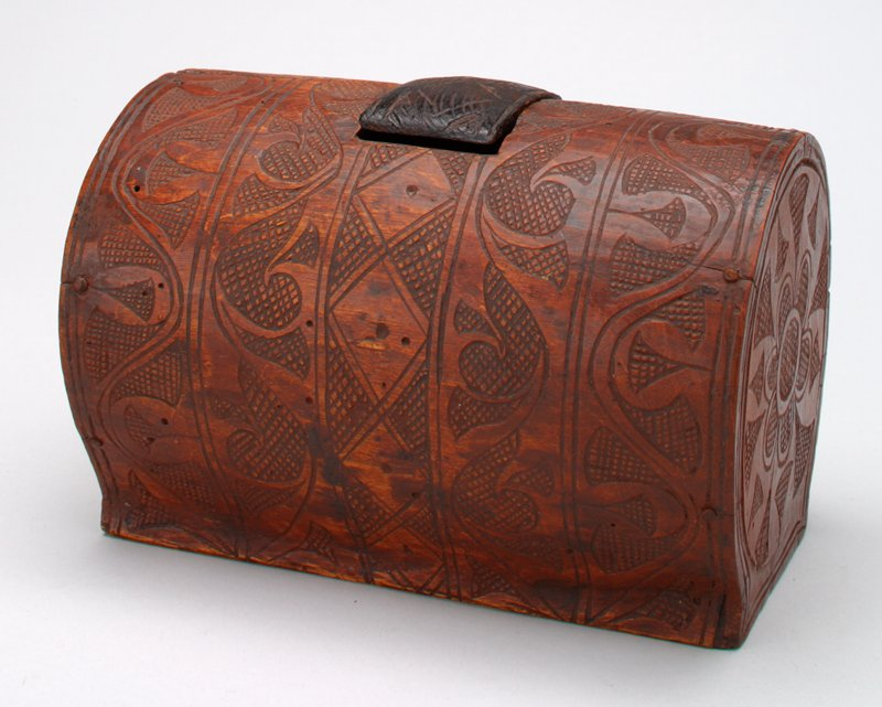 tubular shape with flat foot; incised overall with curving and cross-hatched designs; rectangular opening at top with lid piece (b) in darker wood