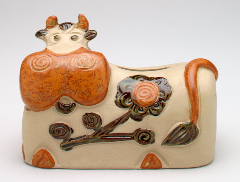 ceramic lying cow; cow's body is unglazed; horns, muzzle, tail and feet of the cow are brown; ears, forelock, eyes, tongue and tail tip are shiny black; shiny black flower with a brown center on the front and back of the cow; coin slot on the back; rubber stopper on bottom