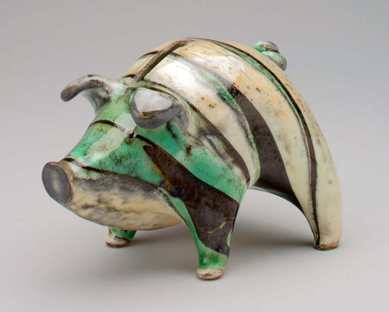 ceramic pig bank with green, black, grey and ivory stripes; glaze is shiny; ears curl forward; pig has a very curly tail; back legs wide apart and taller than front legs causing it to appear to lean forward; little black eyes; chin goes directly from nose to belly