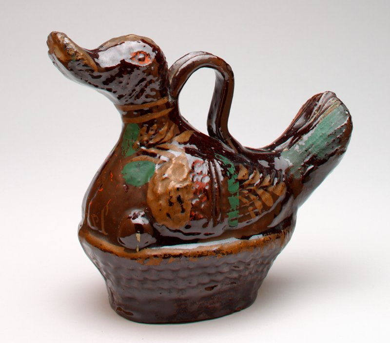 ceramic duck with shiny brown glaze and red, green and gold overglaze painting, sitting on a nest; duck has a handle on top and a coin slot at the top of one side