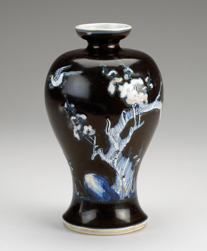 blue and white with dark brown ground on body; blossoming tree with rock and two birds; wide base tapering inward, then outward to shoulder; small spool mouth