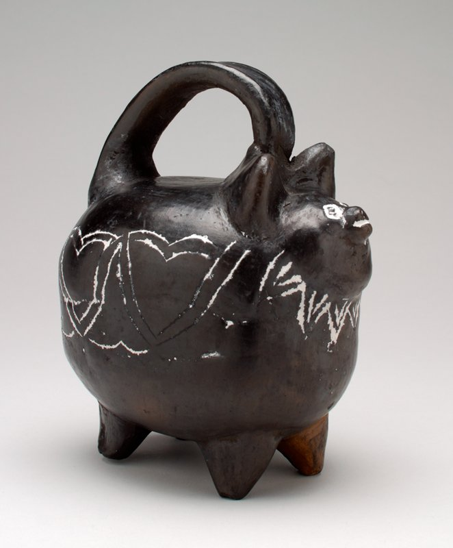 ceramic pig with black glaze; decoration is incised and lines are filled with white pigment; pig body is very rounded with short legs; handle at top; coin slot on the top PL side; heart shapes decorate the body; collar with points decorates the neck; eyes and mouth outlined with white