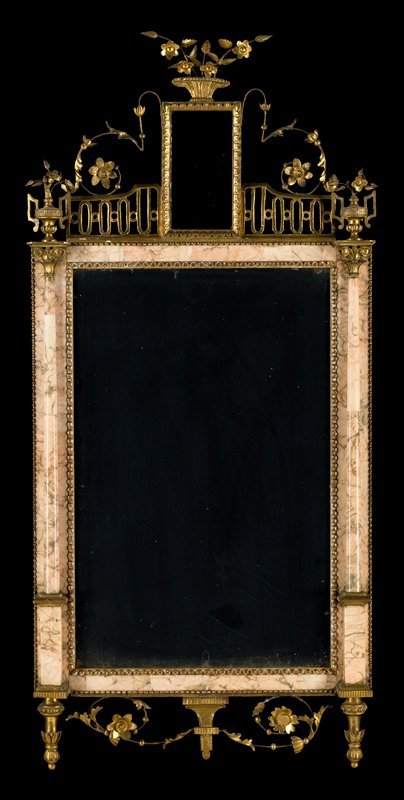 Bilbao Mirrors, pair, marble mosaic veneer, delicate shade of pink; gilded bead and reed molding next to glass. In the open work crest, wire scrolls, leaves and flowers surround oblong insert of veneer. The engaged columns in paneled inserts are surmounted by flower basket finials with characteristic leaf pendants below.
