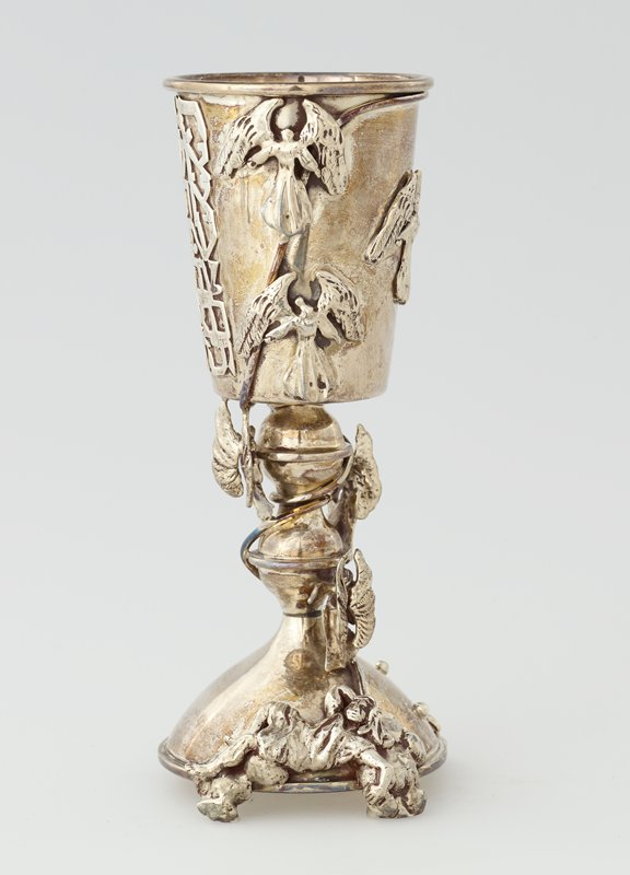 stemmed cup on 4 feet on base; reclining applied figure on base connected by spiraling wire to 5 angels on stem and cup; 1 additional angel on cup; relief applied Hebrew text on cup; balls on cup and base