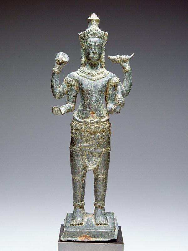 standing male figure with 4 arms, each holding an object; wearing bracelets, heavy earrings, necklace and anklets; attached to mount