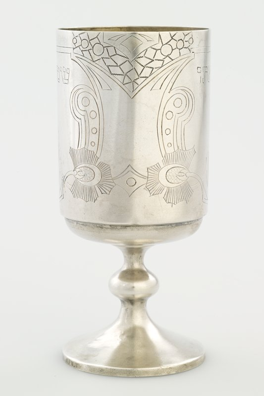 cup with straight sides on a footed stem; incised organic design frames one line of Hebrew text