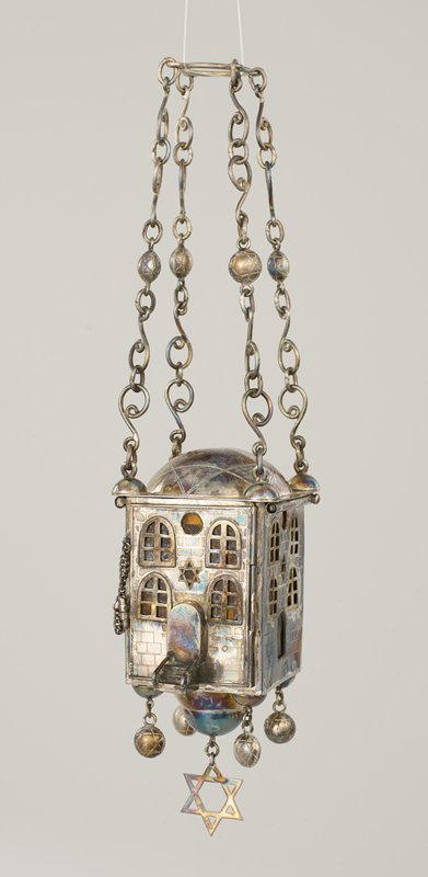 upper canopy section with 4 hanging chains connected to a ring; building-shaped section hanging from 4 chains connected to a ring; sides of building have amber glass panels at interior; hanging chain with 2 large ornaments and 3 small balls; two balls hanging from hooks; one hanging candleholder(?); 8 small pails