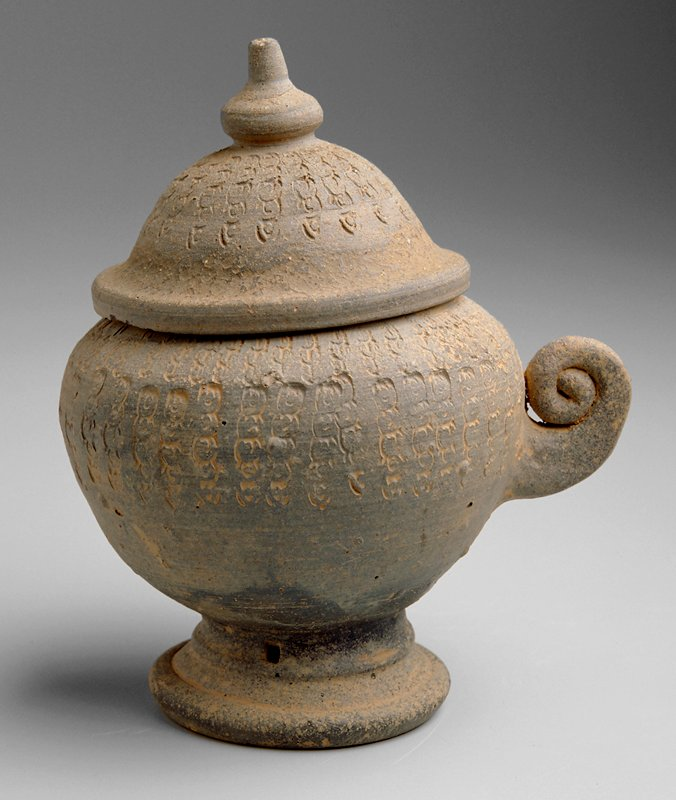 round-bodied jar with a small foot; dome lid and dome finial; one applied spiral coil handle; decorated with repeating stamped design