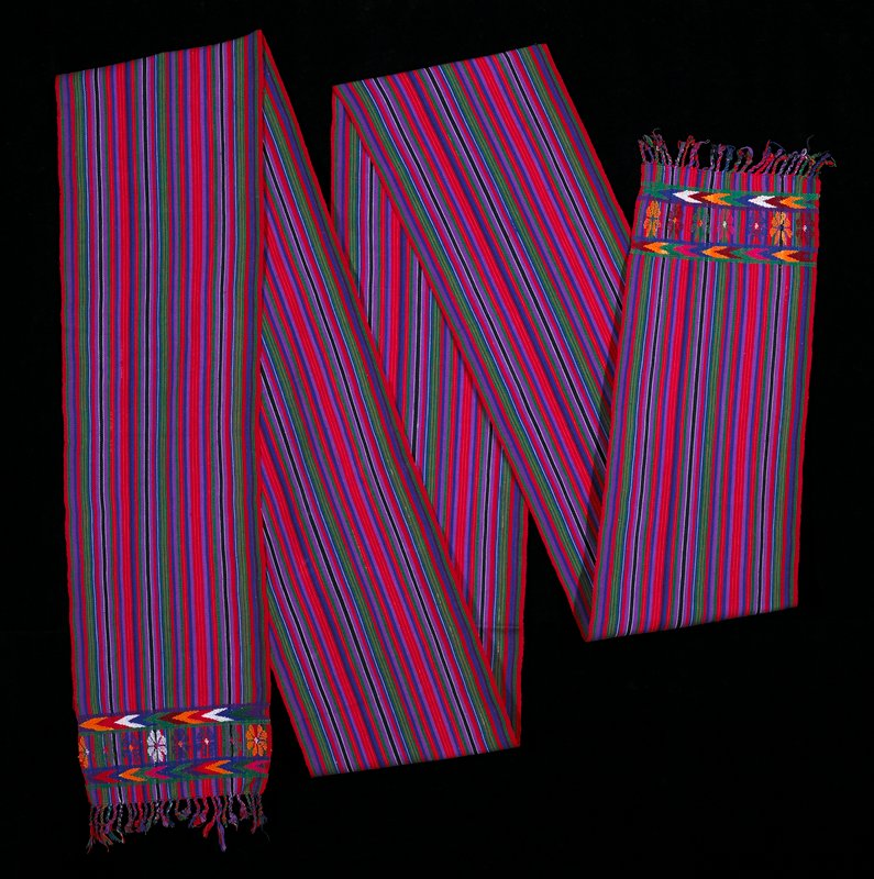 One-paneled sash; woven on a back strap loom; geometric and floral designs on both ends are woven in the one face and double face brocade techniques; red, orange, green, purples, blue, black, white and maroon striped