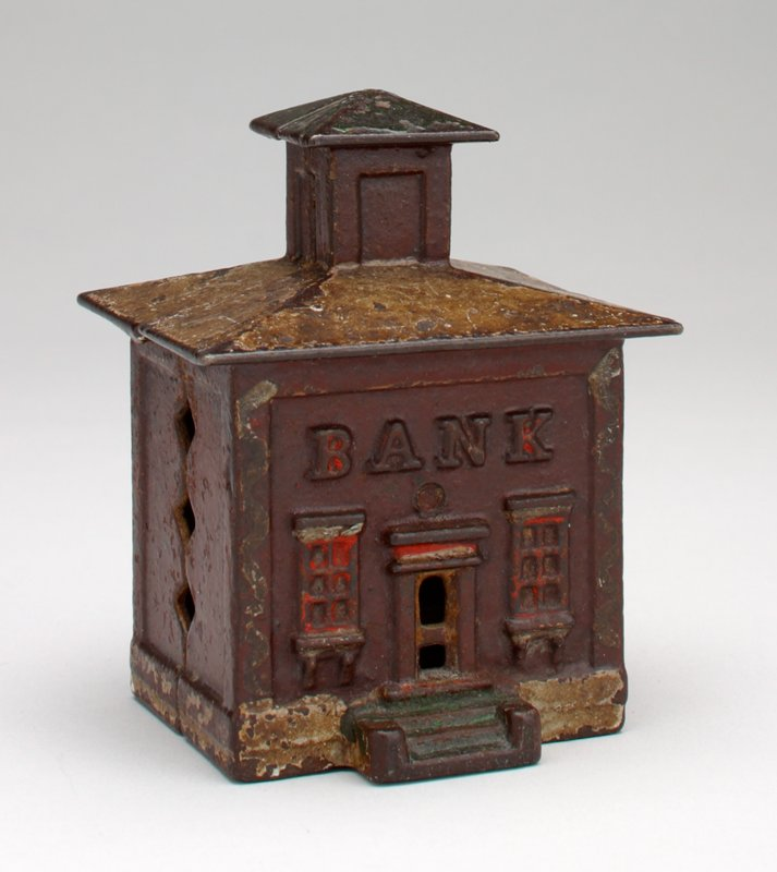 brown rectangular block building; door and two windows in front; coin slot in back; tower (cupola); traces of red and gold pigment