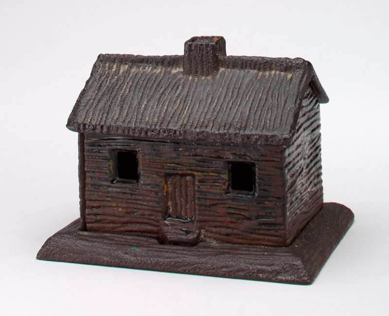 thatched roof; chimney; 2 windows and door; several holes in varying sizes in bottom; remnants of yellow, orange and black paint on front side and back
