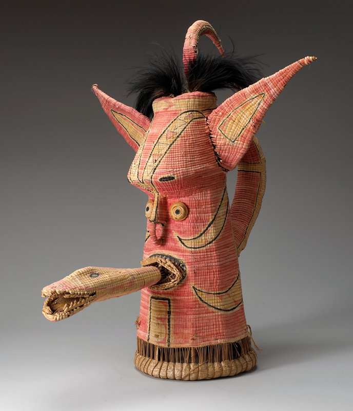 "tapering from wide base; face with protruding eyes, open mouth, protruding forehead; very large fox-like high ears; looping ""handle"" on back of head; separate snake head may have originally protruded from mouth; pink with black linear designs"