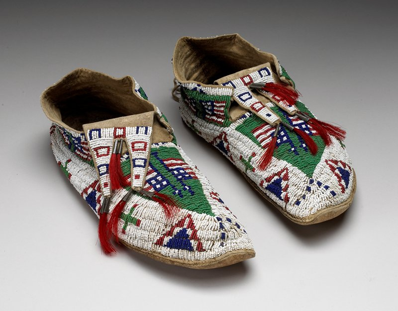 uppers beaded overall in green, white, blue and red with American flags, triangles, crosses and squares; 3 pairs of red tassels on tongues
