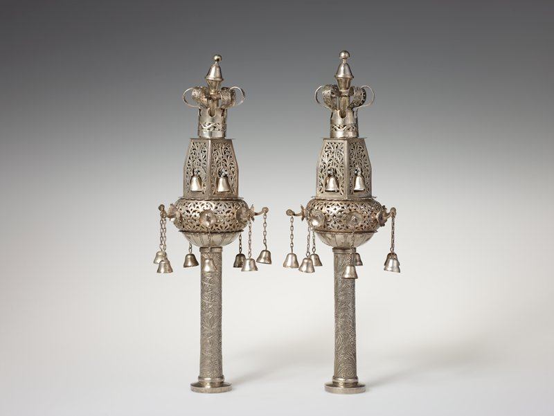 open cutwork tops; four bells hang from the tower and seven more from lower circular section of openwork finial; openwork crowns at top; inscribed floral pattern to stem