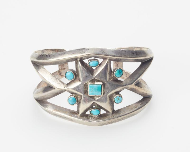 cast openwork band; set with one square and six round Nevada turquoises; star design