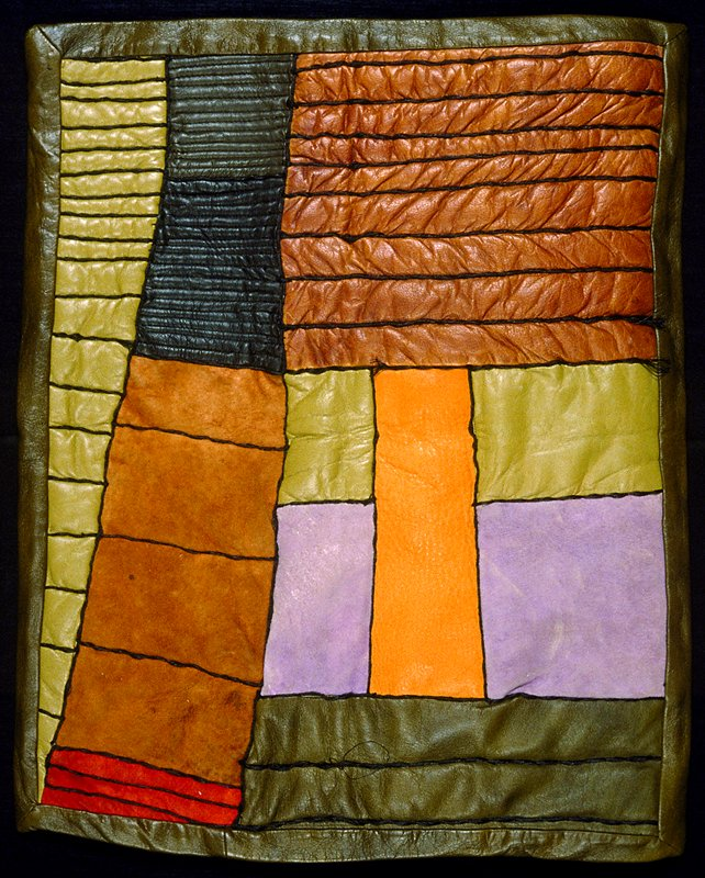 Leather patchwork. Leather patchwork in rust, brown, black, orange & purple. Patches divided with heavy black stitching (brown/black)