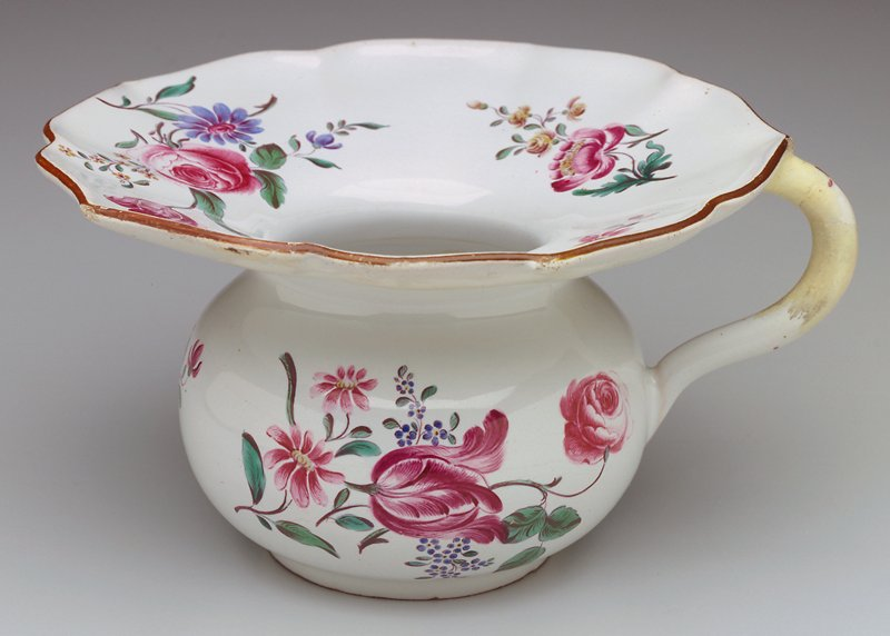 Spitting cup with handle; brown decorations on scalloped edge; sprays of flowers scattered over surface; few yellows, primarily blues and reds; blue underglaze
