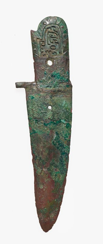 The tang displays a dragon figure, originally inlaid, and a dent in its contour, the origin and meaning of which are obscure. This type of Kuo is quite common, several specimens having come from An-yang. One of the lugs has been broken off this example. Patina green.