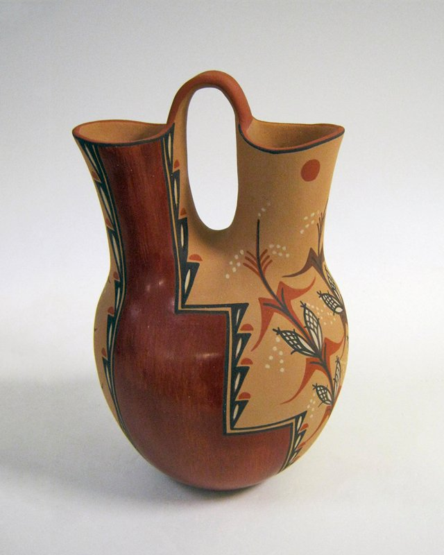 vessel with 2 necks; handle between mouths; tan body decorated with stepped design and 2 corn stalks on each side in red, brown and cream