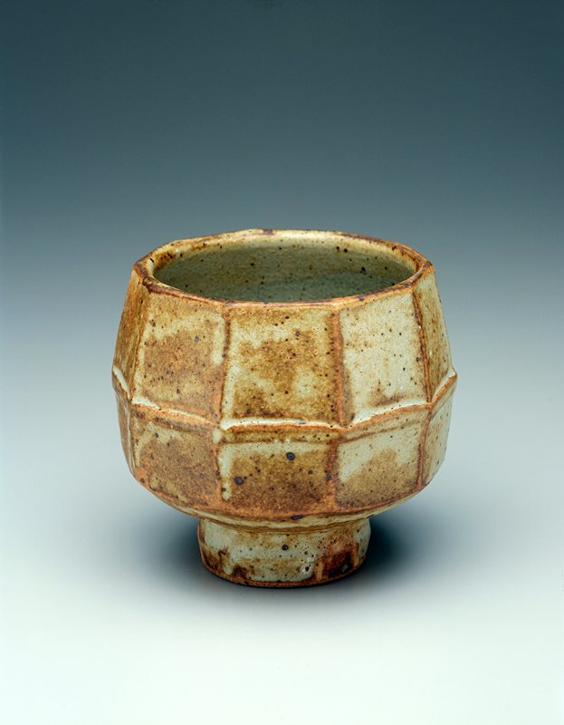 stoneware cup, tall foot, ten sides with a division at center of the body, brownish grey matte glaze overall