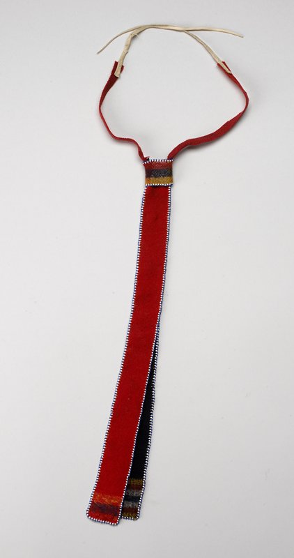 two vertical flannel strips, edged in blue and white beads; one red strip with blue and yellow stripes at bottom, one blue strip with white, red and yellow stripes at bottom; horizontal loop at top creating necktie shape; red ties attached to leather thongs