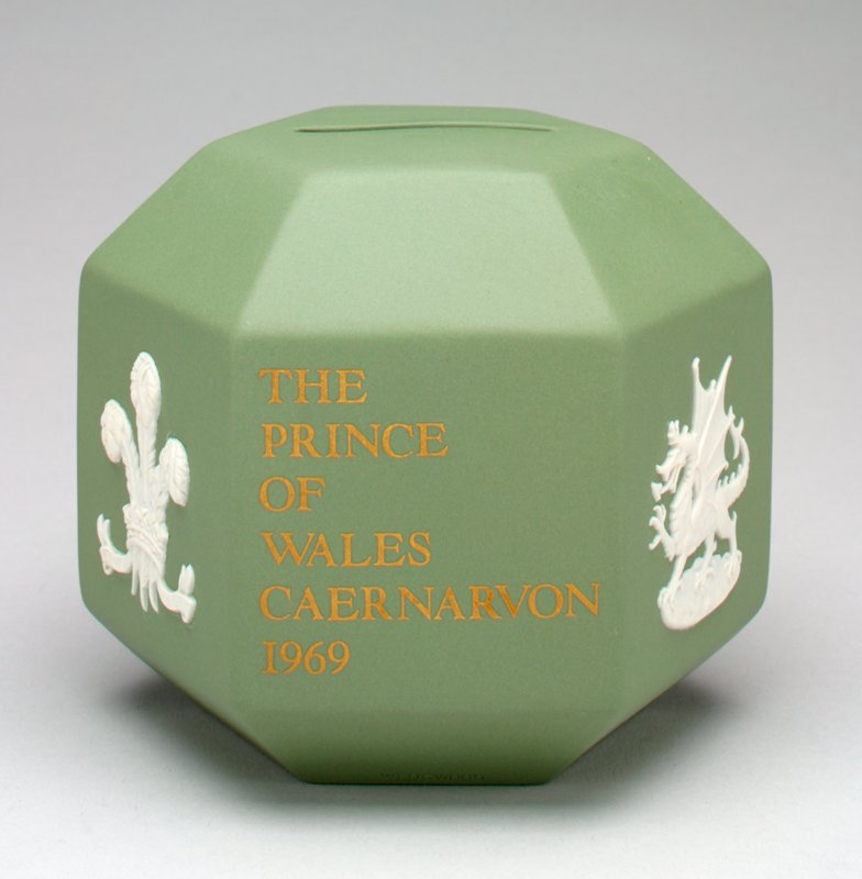 "dull green hexagon with coin slot on top; on one side in gold: ""The Prince of Wales Caernarvon 1969""; on the opposite side the same in Welsh; on two sides, the three feather insignia of the Prince of Wales; on two sides the Welsh dragon insignia; metal stopper on bottom;"