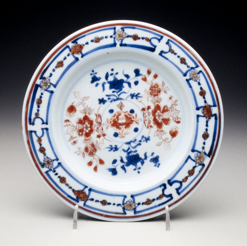 Imari plate with center gilt-heightened iron-red peony sprays, undergalze blue rim with panelled border, divided by gilt and iron-red blossoms and iron-red band