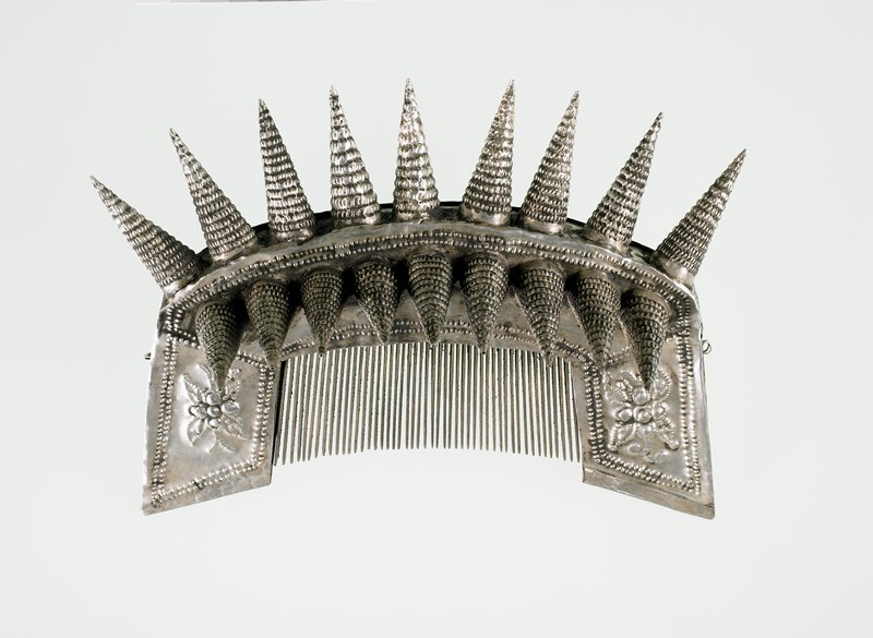 large; silver outer body with top and front cone-shaped spikes; body decorated with hammered dot and floral designs; wood teeth