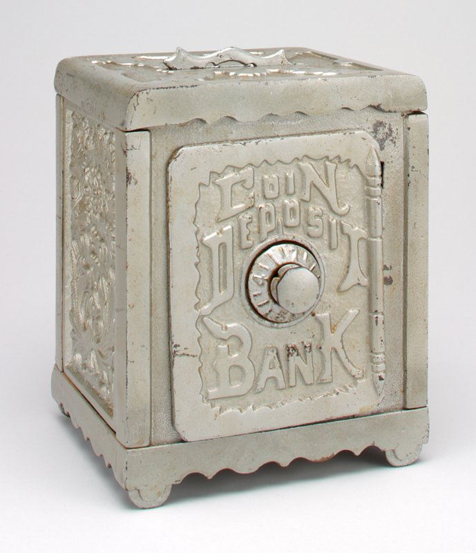 silver metal box in shape of safe; coin slot on top; floral motifs with grapes on both side and back; coin slot on top