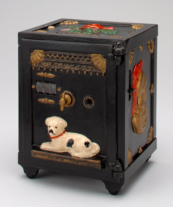 rectangular black metal safe on 4 feet; Roman soldiers on 2 sides; red bird with nest on top; lying dog on front; combination cylinders and handle on front