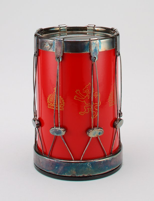red rum with gold lions and crowns on the sides; top, bottom and wires connecting them are silver plate; drum sits on a thin black plastic base