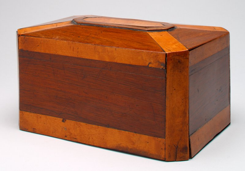 wood box of several woods, light and dark; light strips on corners and around base appear to be veneer; octagonal raised section in lid; coin slot in top below raised section