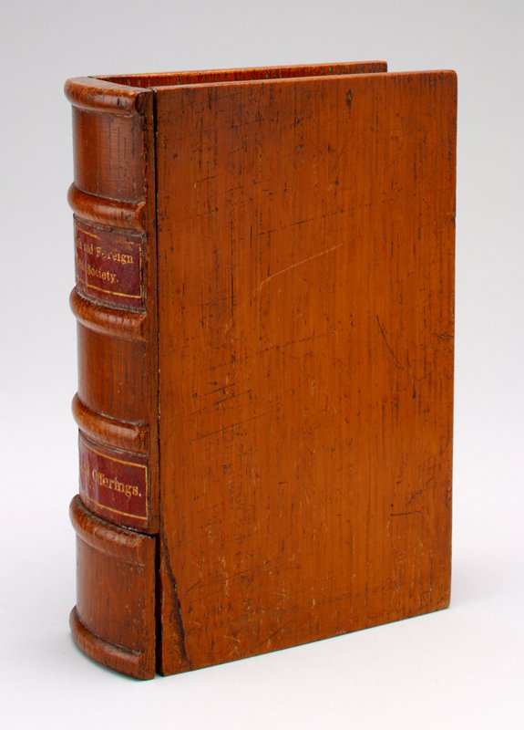 """wooden book stained nut brown with labels on spine of red paper with gold lettering: """"English and Foreign Bible Society"""" is the top label; """"Thank Offerings"""" is the bottom label; a drawer at the bottom of the spine slides out; coin slot at top"""