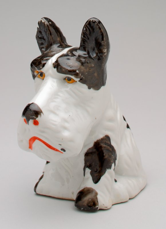 seated sad-eyed white Scottie dog with black spots; dog has yellow eyes, red nostrils and a red mouth; coin slot at back of head; shiny glaze finish