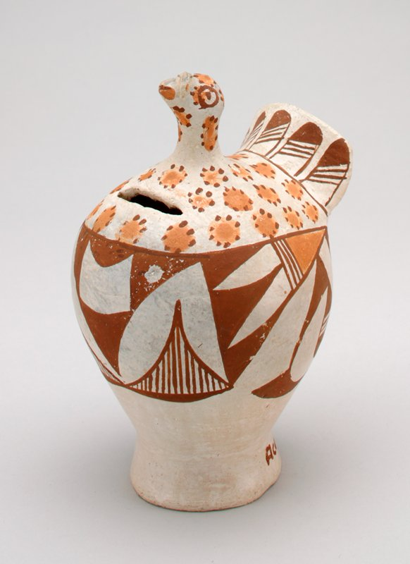 tan bird with dark brown and golden brown designs; coin slot in breast; traditional designs of flowers, feathers etc.