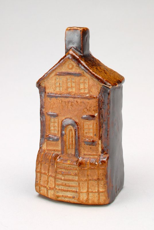 ceramic house tan with brown trim and brown sides and back; coin slot in back