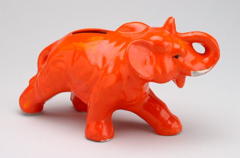 walking orange ceramic elephant, painted silver tusks; trunk curled up to head; coin slot in back
