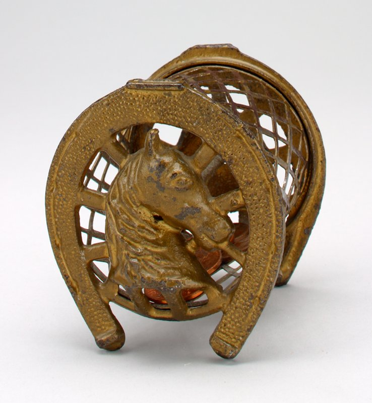 wire mesh cage attached to horse shoes with heads of horses at center of shoes; wire mesh depresses on one side at seam to form coin slot
