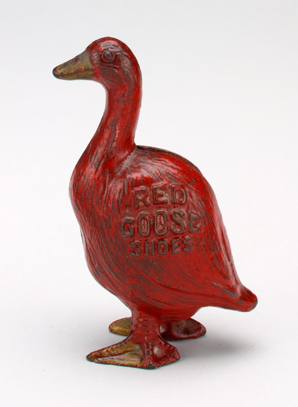 """red metal goose with gold beak, feet and lettering on wings; """"Red Goose Shoes"""" is printed in raised letters on each wing; the bank is made in 2 sections held together by a screw; coin slot on back behind neck"""