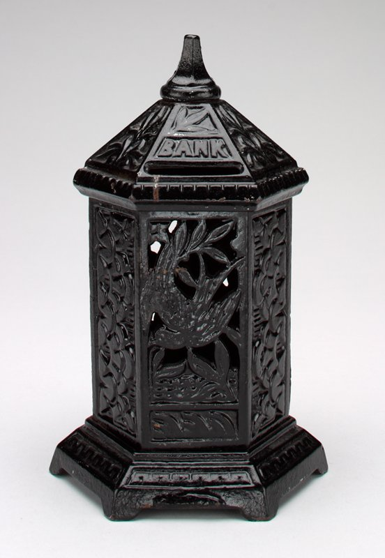 """black metal 6 sided pagoda shape bank; 4 sides are closed work decorated with cloud shapes; 2 sides have open work birds and branches; geometric motif around the base and plant motif around the top; 2 coin slots on top with """"Bank"""" printed above"""